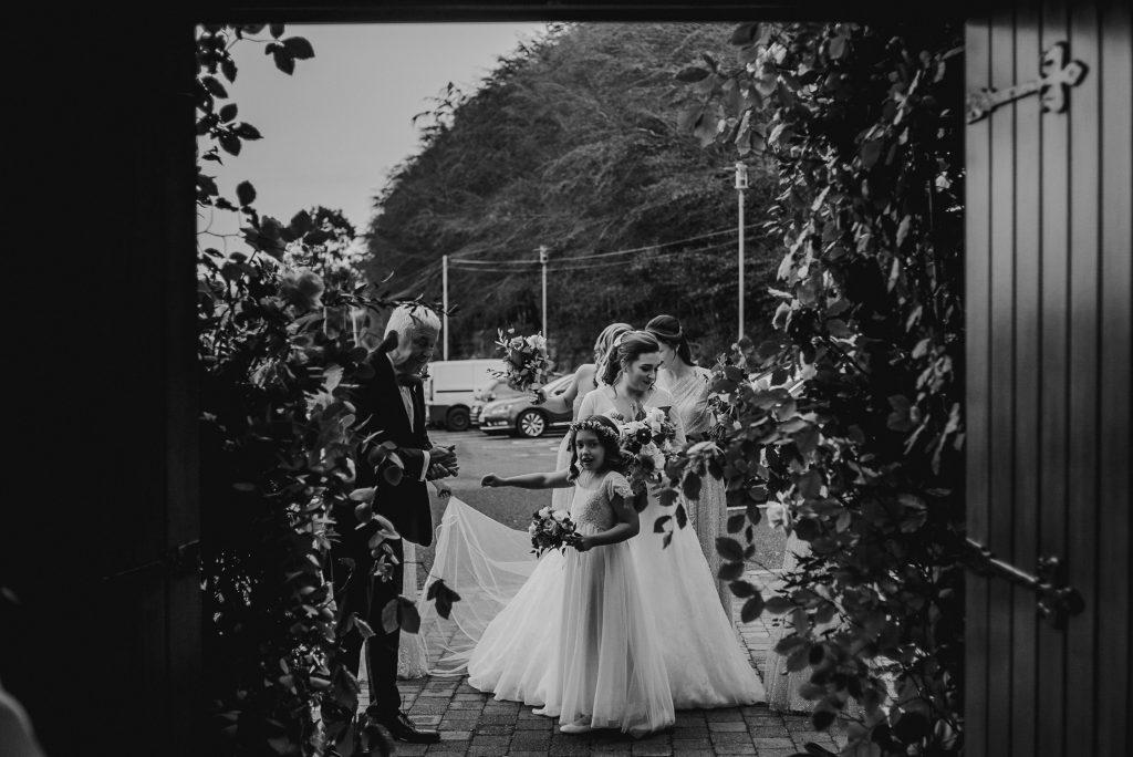 bride standing outside chapel ready to walk in