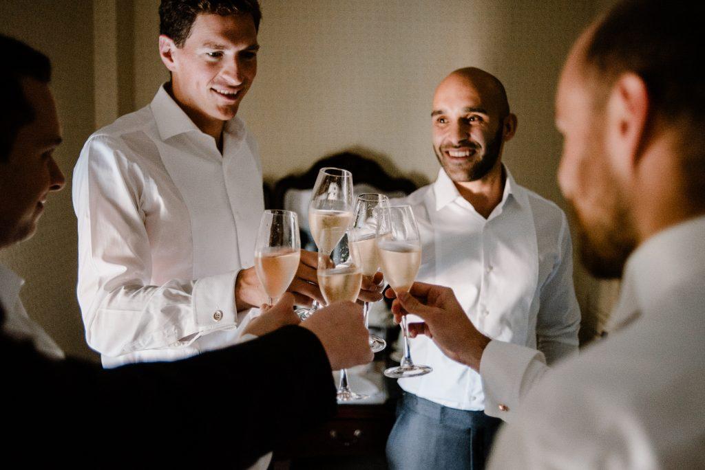 groomsmen doing cheers with drinks