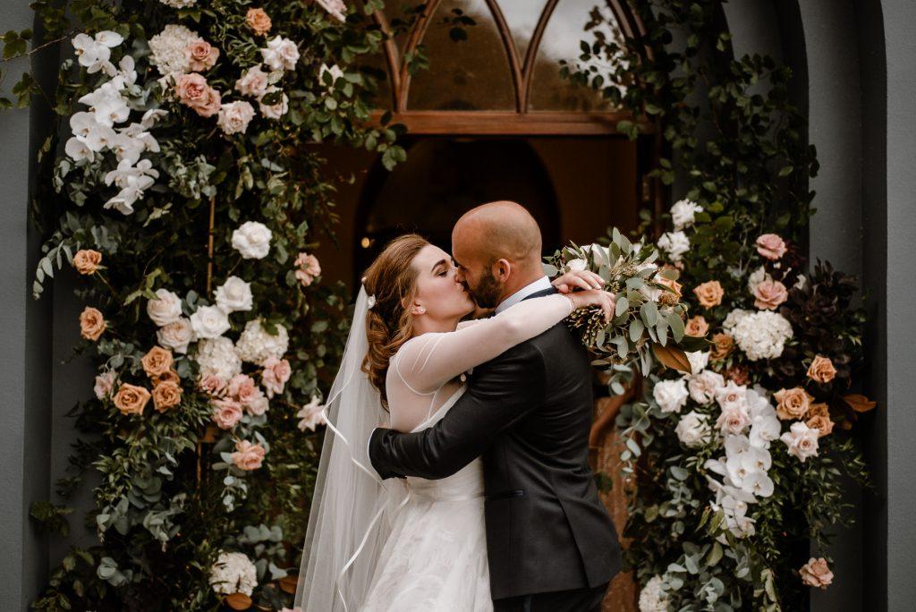 bride and groom kissing outside chapel
