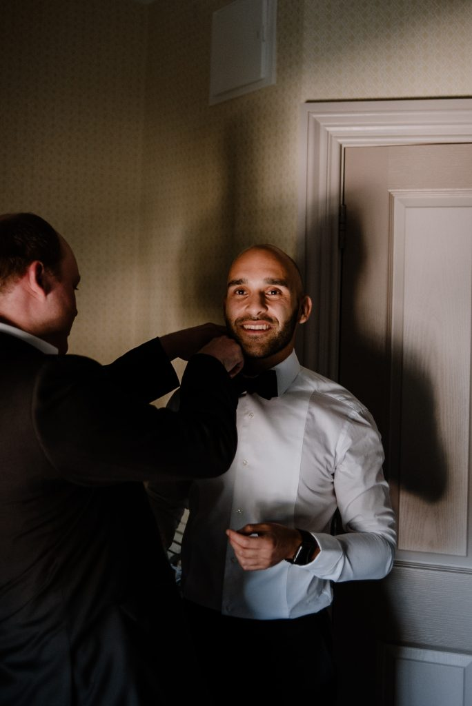groom getting bow tie done