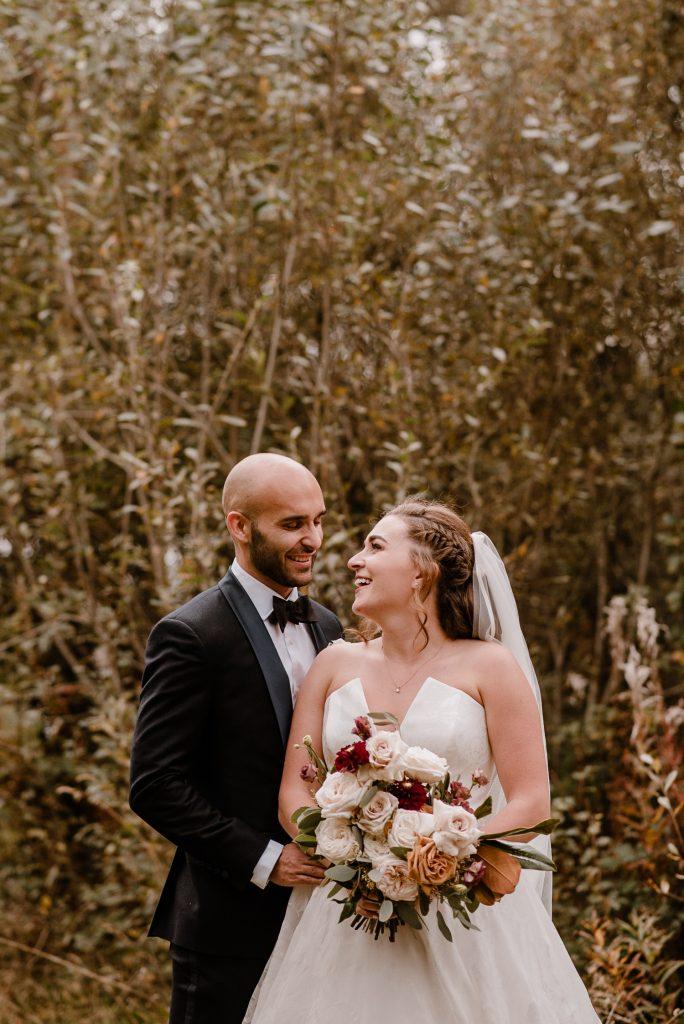 groom standing behind bride smiling hugging her
