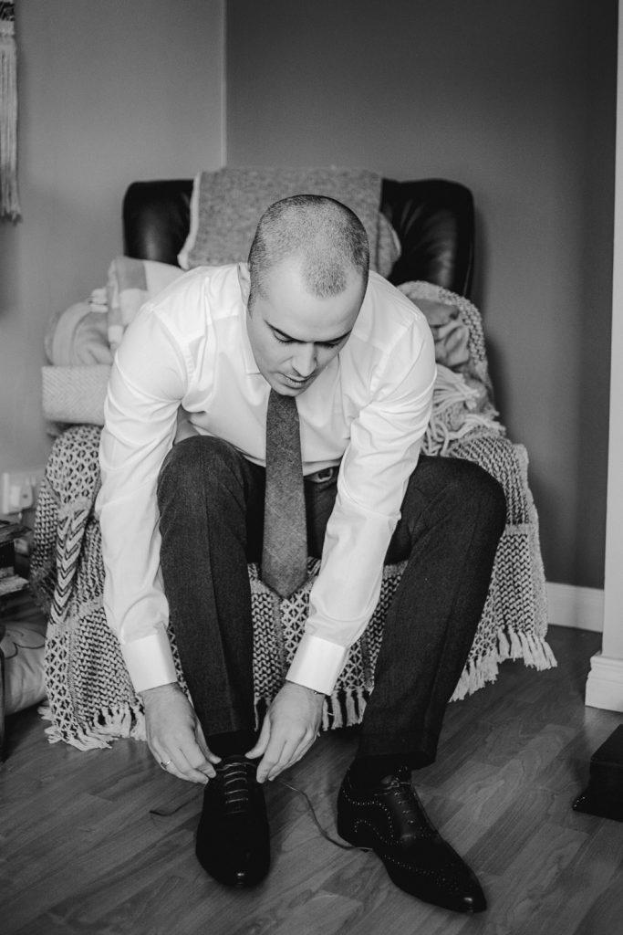Groom tying shoe laces